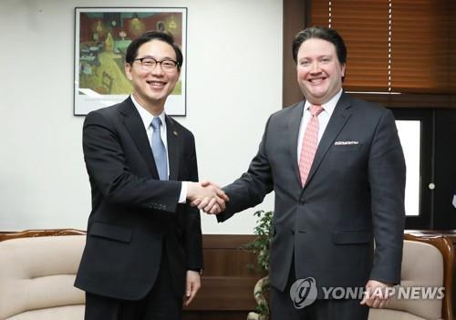 2月14日下午,在首尔中央政府大楼,统一部次官(副部长)千海成(左)同美国驻韩大使代理马克·卡纳佩举行会谈前握手。(韩联社)