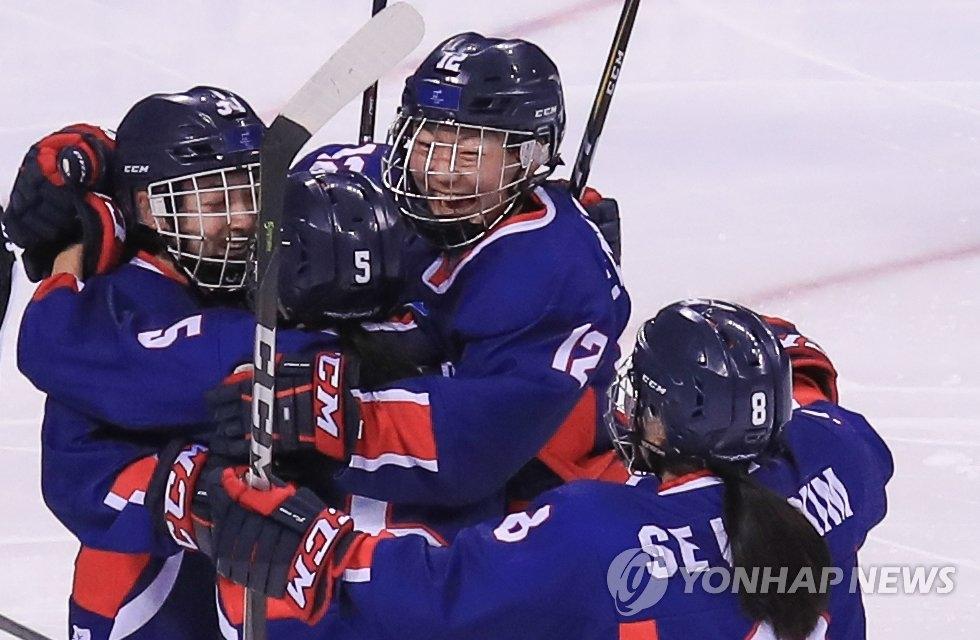 2月14日,在江原道关东冰球中心举行的冬奥冰球女子B组小组赛韩朝联队和日本队比赛中,韩朝联队攻入一球后与队友拥抱庆祝。(韩联社)