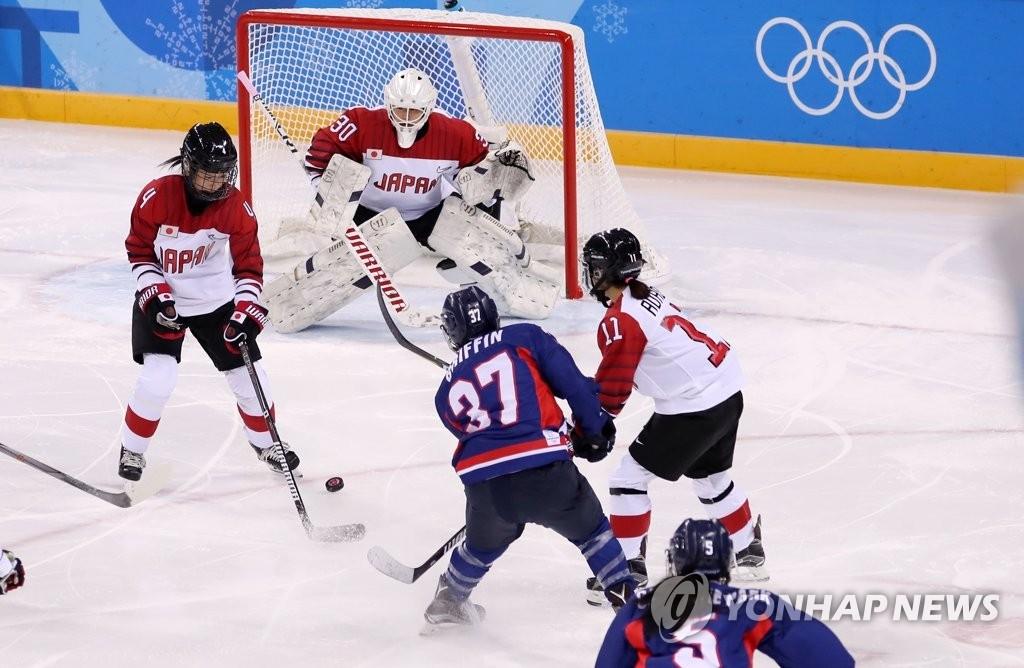 2月14日,在江原道关东冰球中心举行的冬奥冰球女子B组小组赛韩朝联队和日本队比赛中,韩朝联队攻入一球。(韩联社)