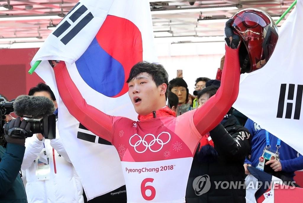 2月16日,在平昌奥林匹克滑行中心,尹诚彬在平昌冬奥会钢架雪车项目比赛结束后向观众挥手致意。(韩联社)