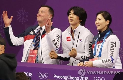 2月16日,在江陵冰上运动场,参加花样滑冰男单短节目比赛的韩国选手车俊焕(中)在表演结束后确认自己的分数。(韩联社)
