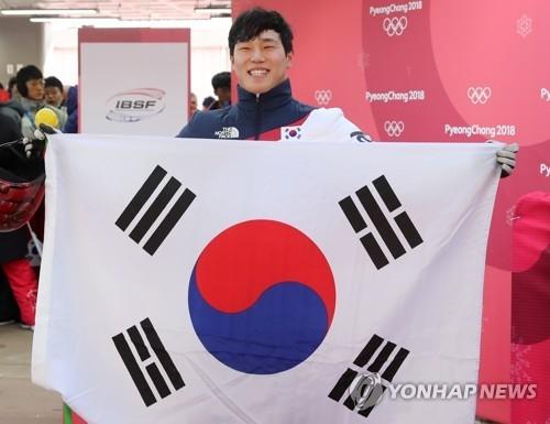 尹诚彬在比赛结束后手举国旗留影。(韩联社)