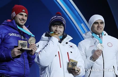 2月16日,在江原道平昌奥运奖牌广场,平昌冬奥会钢架雪车男单金牌得主、韩国选手尹诚彬站在领奖台上。左边为获得铜牌的英国选手多姆·帕森斯,右边为获得银牌的俄罗斯奥林匹克选手尼基塔·特列古博夫。(韩联社)