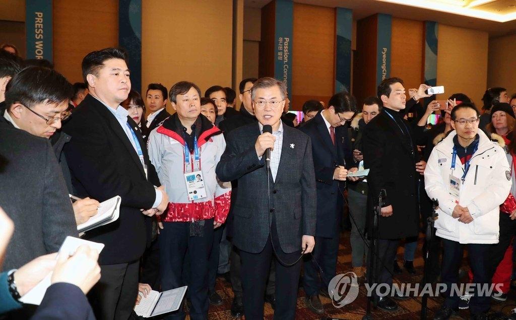 2月17日,在平昌冬奥会主新闻中心,韩国总统文在寅(手拿麦克风)进行发言。(韩联社)