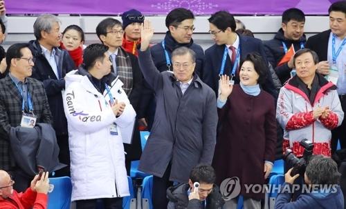 2月17日下午,在江原道江陵冰上运动场,韩国总统文在寅(第二排右三)和第一夫人金正淑女士(第二排右二)到场观看2018平昌冬奥会男女短道速滑比赛,并向一同观赛的观众挥手致意。(韩联社)
