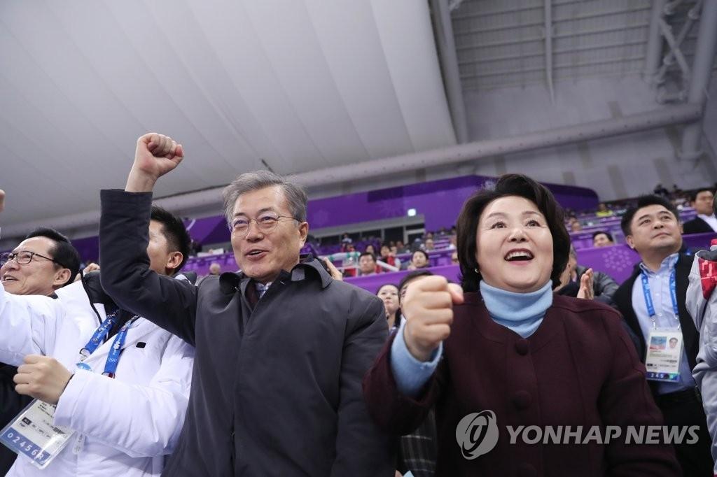 2月17日,在江陵冰上运动场,韩国总统文在寅偕夫人金正淑观看2018平昌冬奥会短道速滑比赛。图为总统夫妇为韩国短道速滑名将崔珉祯摘取女子1500米金牌欢呼。(韩联社)