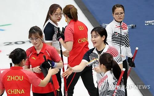 2月18日,在江原道江陵冰壶中心,韩国女子冰壶队(白色上衣)和中国队选手们在比赛结束后握手致意。韩国女子冰壶队在当天下午进行的循环赛第五轮较量中以12比5的比分战胜中国队。(韩联社)