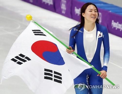 2月18日,在江原道江陵速滑馆,韩国选手李相花在平昌冬奥会速滑女子500米比赛结束后挥舞国旗向观众致意。(韩联社)