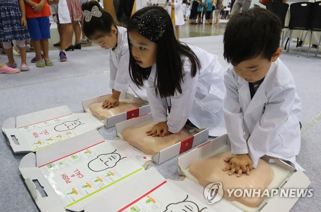 资料图片:孩子们体验当医生。(韩联社)