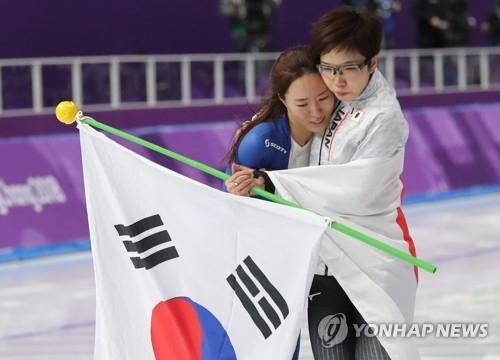 2月18日,在江陵速滑馆,李相花(左)与小平奈绪在平昌冬奥会速滑女子500米比赛结束后相拥在一起。(韩联社)