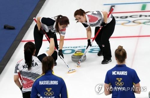 2月19日,在江陵冰壶中心,韩国队与瑞典队在进行平昌冬奥会冰壶女子预赛。(韩联社)