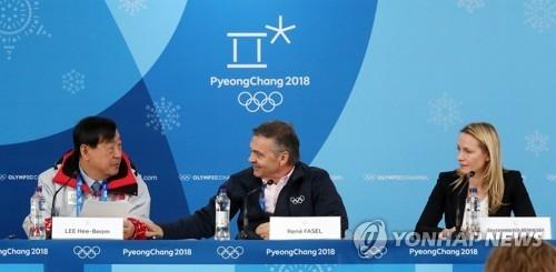 2月19日上午,在江陵冰球中心,李熙范(左)和法赛尔(居中)在国际冰联平昌冬奥女子冰球赛中期记者会上交谈。韩联社