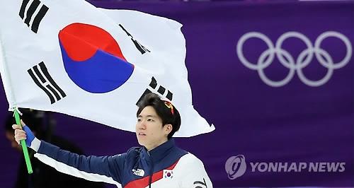 2月19日,在江陵速滑馆,平昌冬奥会速滑男子500米项目银牌得主车旼奎挥舞国旗向观众致意。(韩联社)