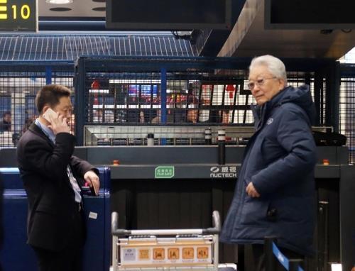 张雄(右)在机场办登机手续。(韩联社)
