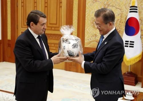 2月20日下午,在青瓦台,列维京(左)向文在寅赠送俄罗斯世界杯用球。(韩联社)
