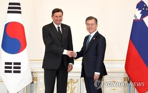 2月20日,在青瓦台,韩国总统文在寅(右)会晤斯洛文尼亚总统博鲁特•帕霍尔。(韩联社)