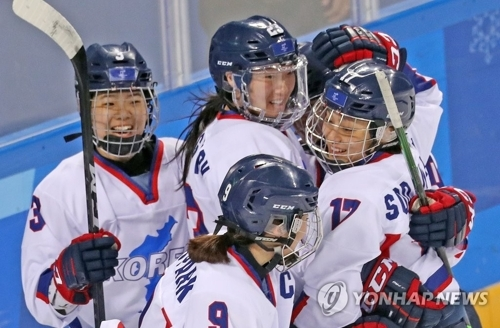 2月20日,韩朝女子冰球联队与瑞士队在江陵关东冰壶中心进行平昌冬奥会第7-8位排名赛,韩朝联队在打入一粒进球后抱作一团。(韩联社)