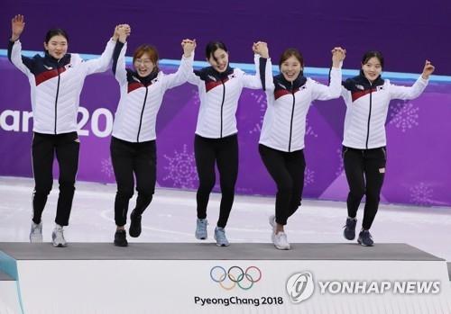 在女子短道3000米接力赛中夺冠的沈锡希、崔珉祯、金艺珍、金雅朗、李有彬登上最高领奖台。(韩联社)
