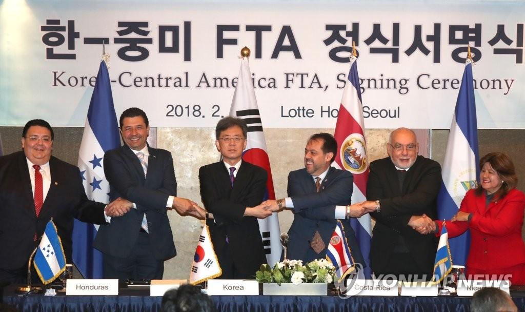 2月21日,在首尔中区乐天酒店,产业部通商交涉本部长金铉宗(左三)与哥斯达黎加、萨尔瓦多、洪都拉斯、尼加拉瓜和巴拿马共5个中美洲国家经贸部长手拉手并合影留念。(韩联社)
