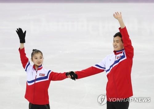 资料图片:2月15日,在江陵冰上运动场,朝鲜花样滑冰双人滑组合廉黛玉(左)、金主植在练习中向现场观众微笑挥手。(韩联社)