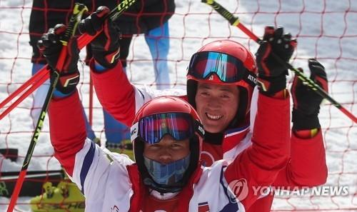 资料图片:2月18日,在平昌龙坪高山滑雪中,参加高山滑雪男子大回转项目角逐的朝鲜选手崔明光(左)和姜成一向朝鲜拉拉队挥手。(韩联社)