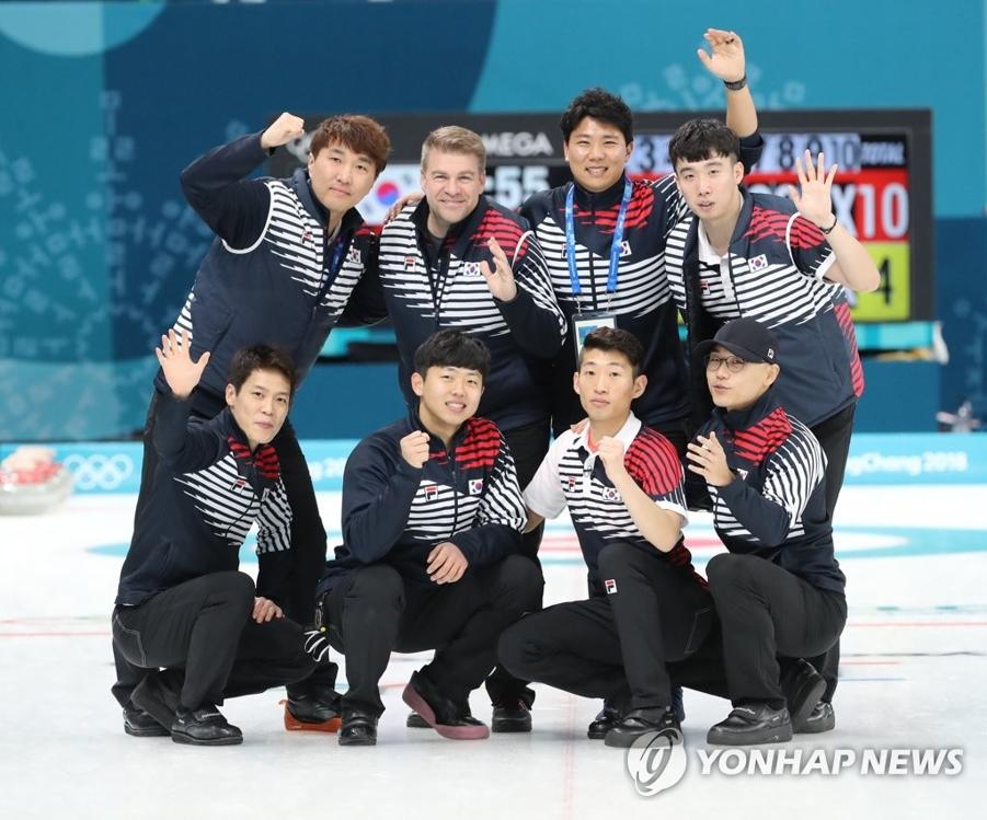 2月21日,在江陵冰壶中心,韩国冰壶男队在结束与日本队的比赛后合影留念。(韩联社)