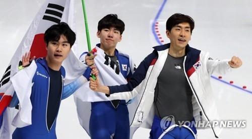 2月21日,在江陵速滑馆,摘得平昌冬奥会速滑男子团体追逐银牌的韩国队队员身披国旗向观众致意。左起依次为金民锡、郑在源、李承勋。(韩联社)