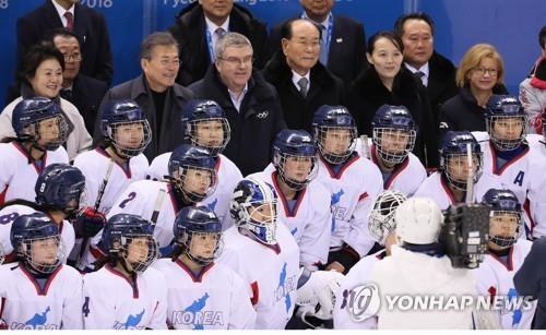 2月10日,在江原道江陵关东冰球中心,韩朝领导人和韩朝女子冰球联队选手们在比赛结束后合影留念。(韩联社)