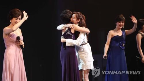 2月11日下午7时,在首尔国立中央剧场,少女时代徐玄(左三)与朝鲜艺术团同台演出后,与朝鲜歌手拥抱。(韩联社)