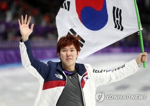 2月23日,在江陵速滑馆,在平昌冬奥会速滑男子1000米项目中摘铜的韩国选手金太润挥舞国旗向观众挥手。(韩联社)