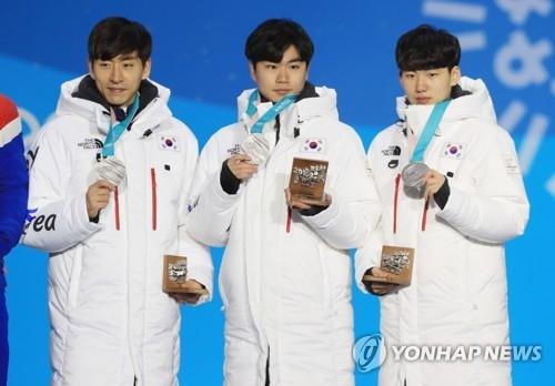 2月22日下午,平昌冬奥速度滑冰男子团体追逐项目颁奖仪式在平昌奥林匹克颁奖广场举行,获得银牌的韩国选手李承勋(左起)、金民锡、郑在源一同站在领奖台上。(韩联社)