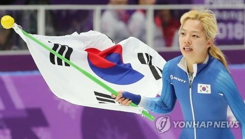 2月24日,在江陵速滑馆,获得平昌冬奥会速滑女子集体出发银牌的韩国选手金宝凛挥舞国旗向观众致意。(韩联社)