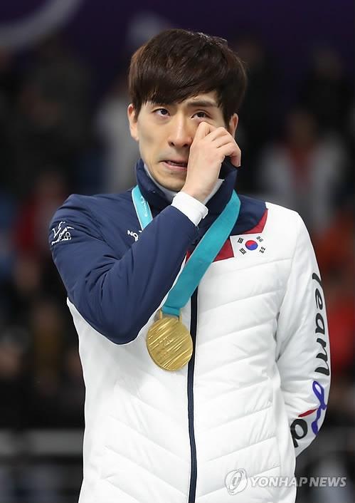 2月24日,在江陵速滑馆,获得平昌冬奥会速滑男子集体出发金牌的韩国选手李承勋在领奖台上拭泪。(韩联社)