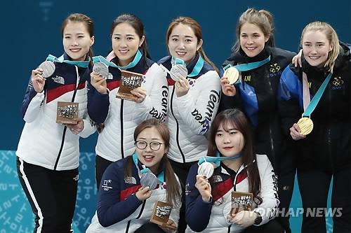 2月25日,在江陵冰壶中心,韩国女子冰壶队在颁奖仪式后与瑞典队合影。(韩联社)