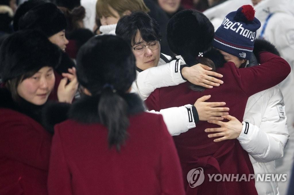 2月26日上午,在江陵运动员村,韩朝女子冰球联队队员们互相拥抱道别。(韩联社)