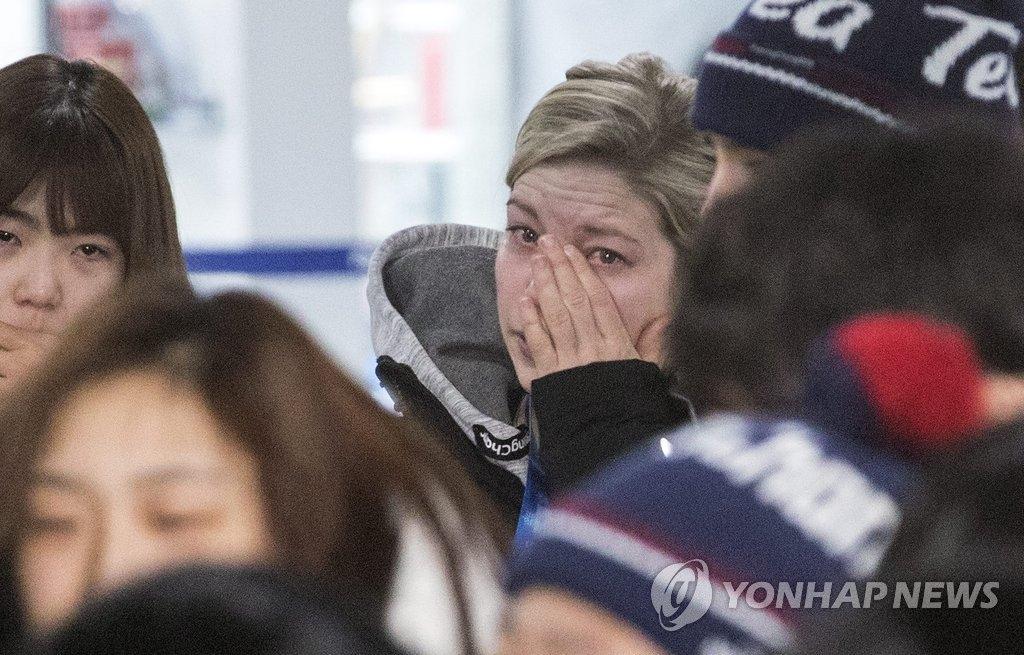 2月26日上午,在江陵运动员村,韩朝女子冰球联队教练萨拉·默里在2018平昌冬奥会结束后与选手们挥泪道别。(韩联社)