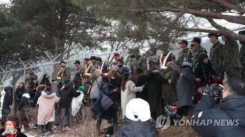 """2月27日,在权志龙入伍现场,依依不舍的BIGBANG歌迷们争相涌向兵营围栏看偶像""""最后一眼""""。(韩联社)"""