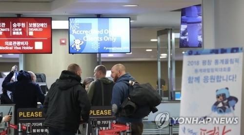 资料图片:1月25日,在仁川国际机场第一航站楼,前来参加平昌冬奥会的外国传媒人士在走专用边检通道。(韩联社)