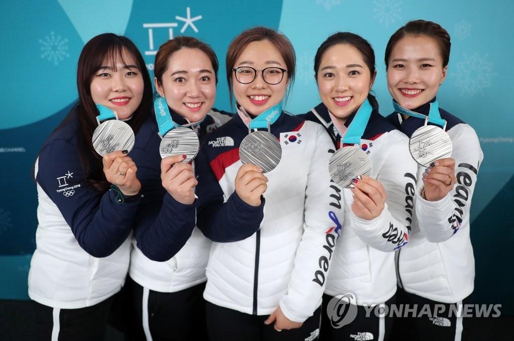 资料图片:2月25日,在江陵冰壶中心,韩国女子冰壶队在2018平昌冬奥会女子冰壶项目中摘得银牌后胸挂银牌合影留念。(韩联社)