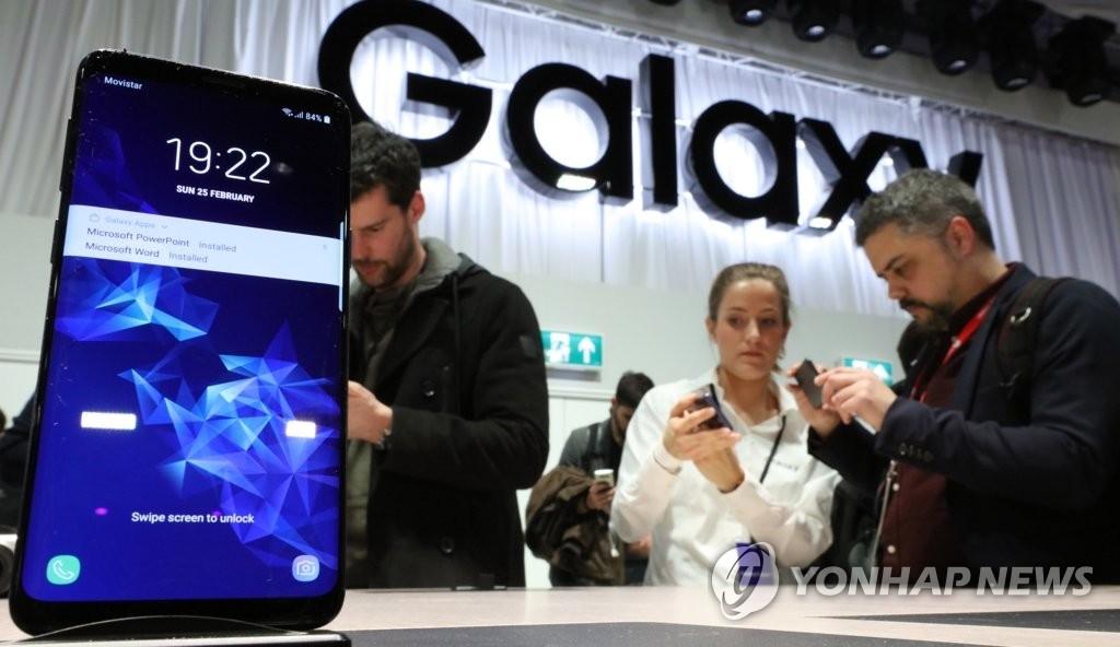 资料图片:当地时间2月25日,在西班牙巴塞罗那举行的三星Galaxy S发布会上,媒体记者体验Galaxy S9和S9+。(韩联社)