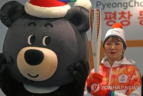 资料图片:展示平昌冬残奥会圣火火炬与火炬手服装的模特站在吉祥物旁边。(韩联社)