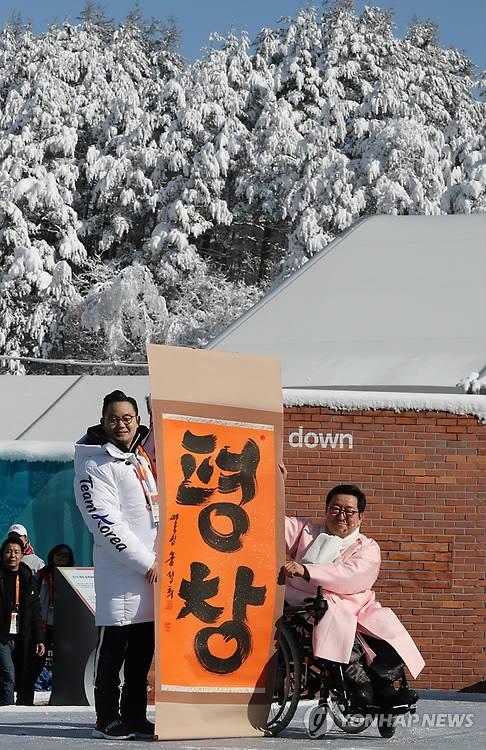 """3月6日上午,在江原道平昌运动员村,村长朴殷秀(右)在韩国体育代表团入村仪式上手持写有""""平昌""""字样的字幅拍照留念。(韩联社)"""