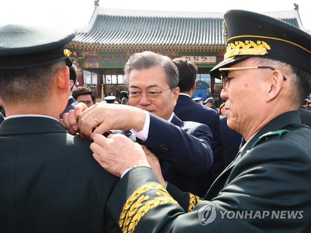 3月6日下午,在首尔泰陵陆军士官学校,文在寅在第74届毕业典礼和授衔仪式上为毕业军官佩戴军衔。(韩联社