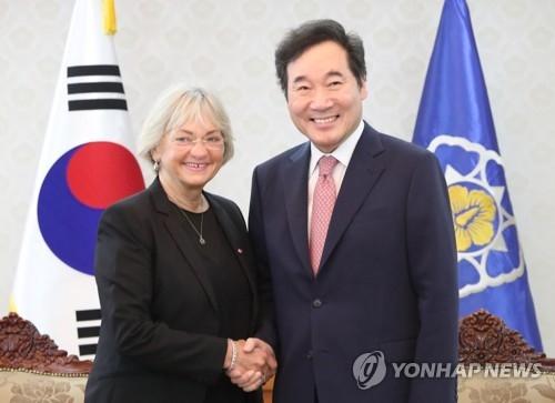 3月6日,在中央政府首尔办公楼,韩国国务总理李洛渊(右)同丹麦国会议长皮娅·柯丝高握手。(韩联社)
