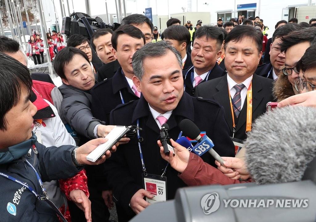 3月7日,在平昌冬残奥会运动员村的国旗广场,朝鲜奥委会代表团团长金文铁(中)面带微笑接受记者采访。(韩联社)
