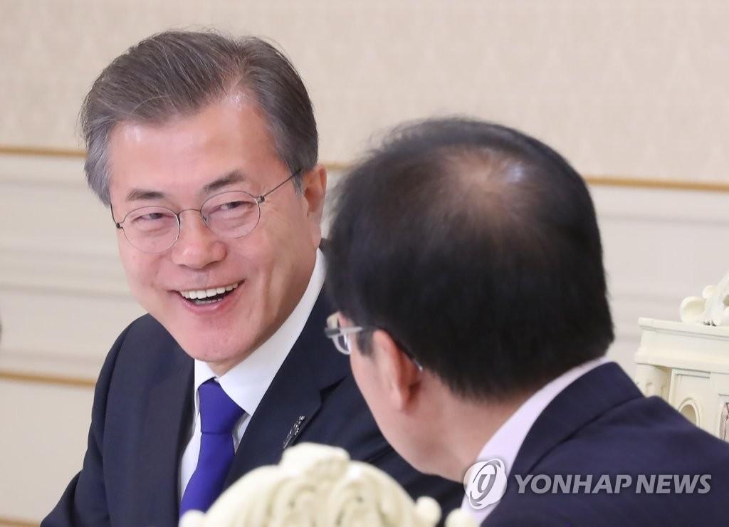 3月7日下午,在青瓦台,韩国总统文在寅邀请韩国朝野五党党首在青瓦台举行午餐会晤。图为文在寅(左)与自由韩国党党首洪准杓交谈。(韩联社)