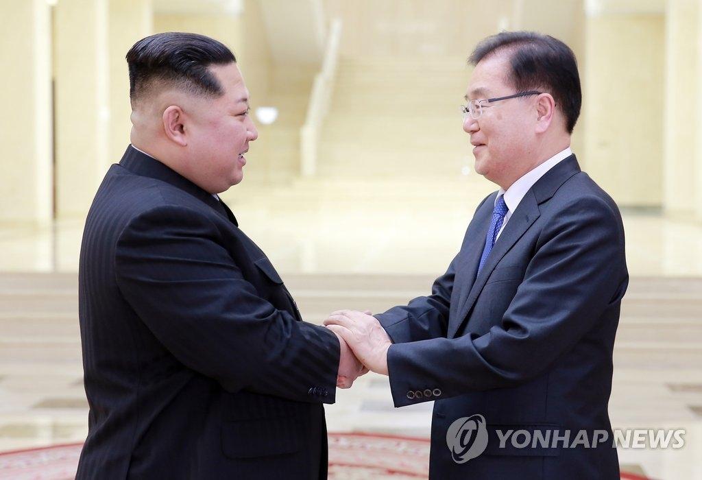 3月5日,在平壤,韩国对朝特使团首席代表郑义溶(右)与朝鲜劳动党委员长金正恩握手致意。(韩联社/青瓦台提供)