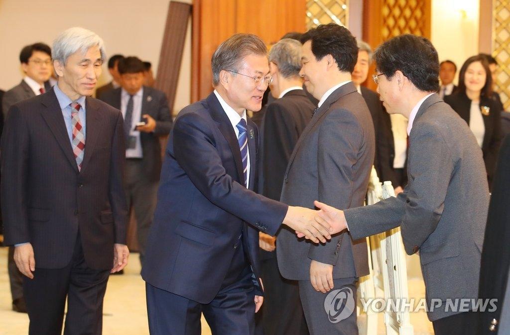 3月13日上午,在青瓦台,韩国总统文在寅出席总统直属政策企划委员会旗下的国民宪法咨询特别委员会午餐会并同委员们握手。(韩联社)