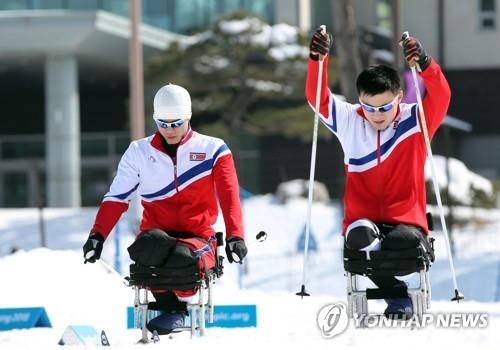 3月10日,在平昌冬季两项中心,朝鲜残疾人运动员马有喆(左)和金正炫正在训练。(韩联社)