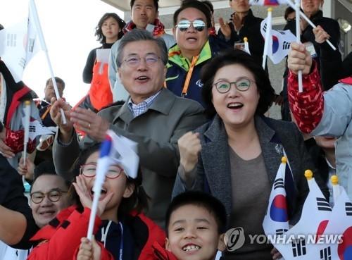 3月14日上午,在江原道平昌冬季两项中心,文在寅和金正淑为残疾人滑雪运动员加油。(韩联社)